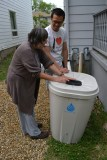 Chris and Lida placing her rain barrel